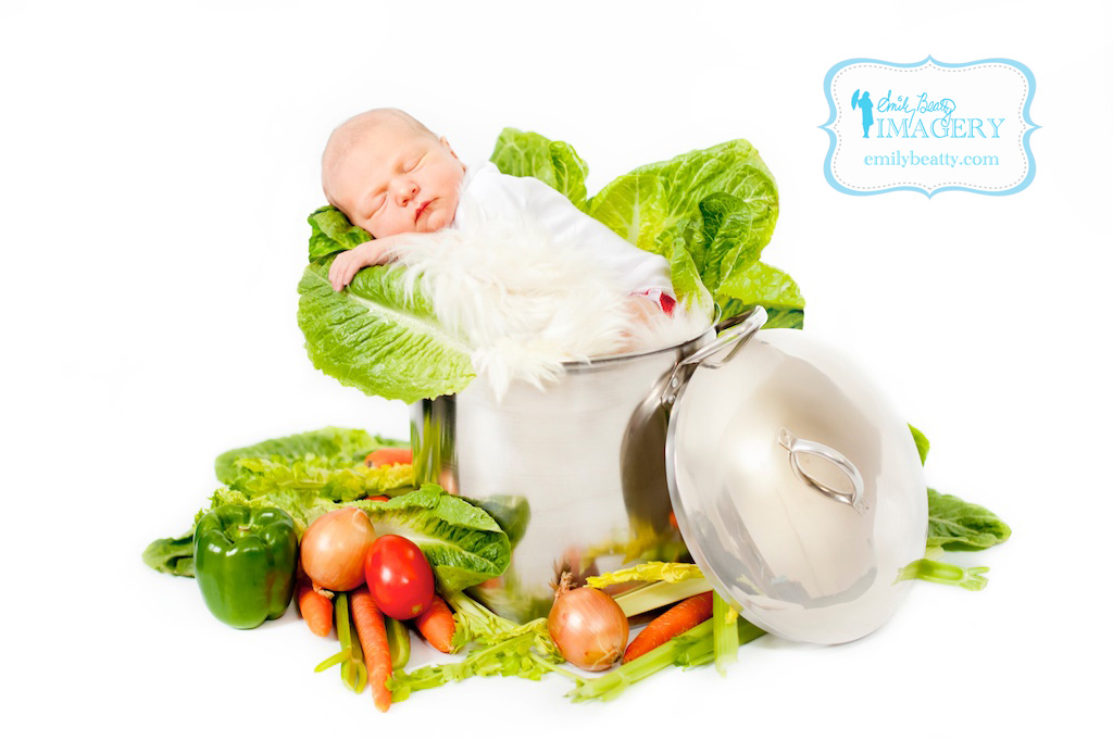 Baby girl in a cooking pot with veggies for a fun baby portrait.