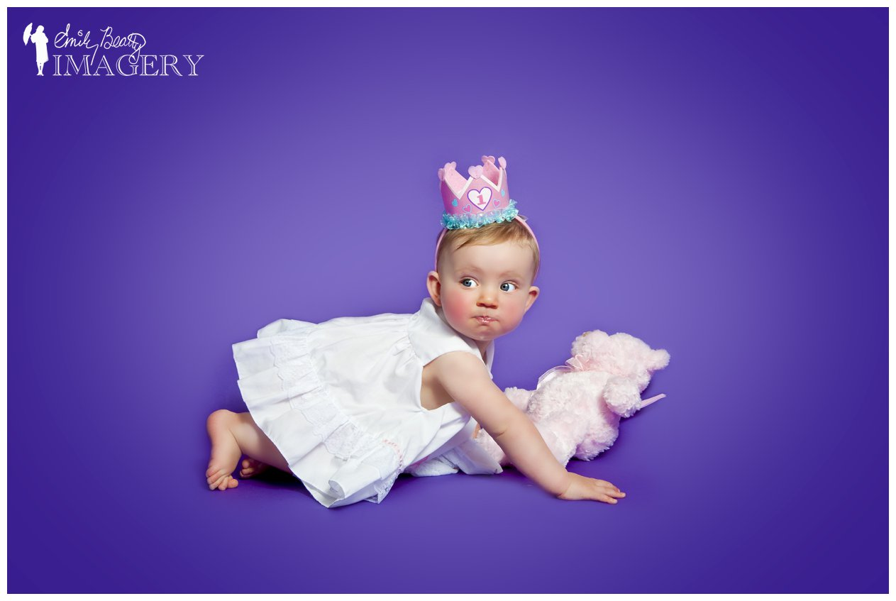 Purple portrait of baby girl with pink teddy bear.